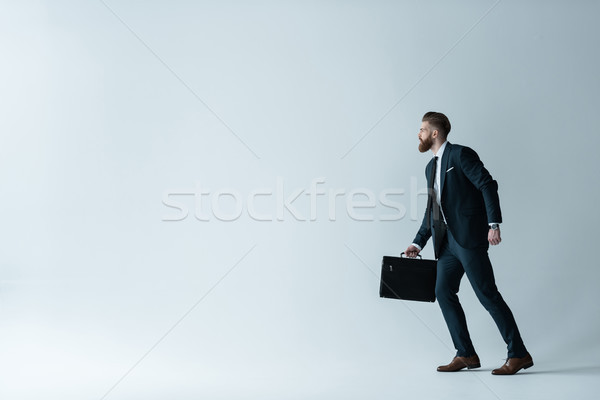 Side view of stylish bearded businessman running with briefcase on grey Stock photo © LightFieldStudios
