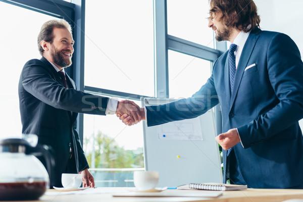 Empresarios apretón de manos dos sonriendo profesional oficina Foto stock © LightFieldStudios