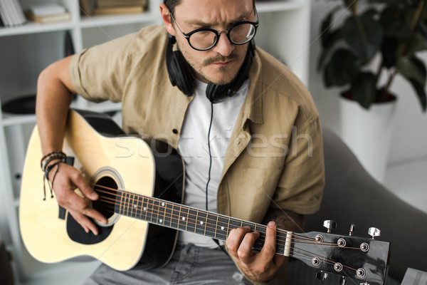 Férfi játszik gitár fókuszált elegáns fejhallgató Stock fotó © LightFieldStudios