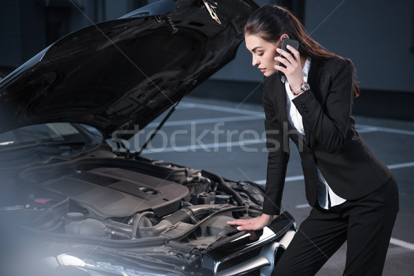 woman looking under hood of car Stock photo © LightFieldStudios