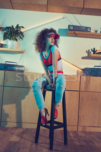 Alla moda donna seduta bar sgabello luminoso Foto d'archivio © LightFieldStudios