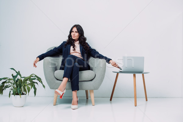 businesswoman relaxing in armchair Stock photo © LightFieldStudios
