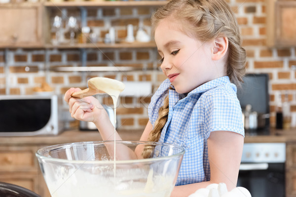 Smiling little girl holding wooden spoon and looking at dough in glass bowl Stock photo © LightFieldStudios