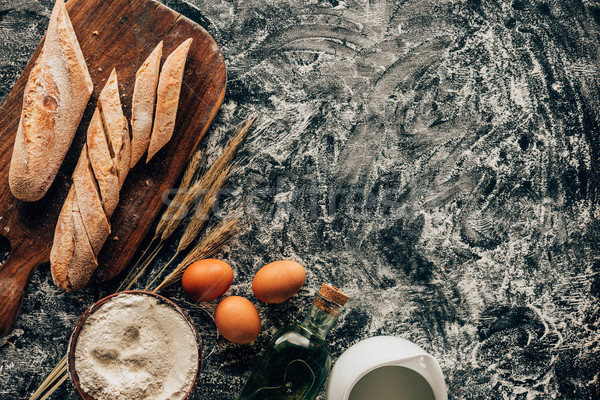 top view of arranged pieces of french baguette, raw eggs, wheat and flour in bowl on dark surface Stock photo © LightFieldStudios