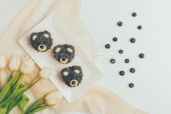 top view of gourmet cupcakes in shape of bears, fresh blueberries and tulip flowers Stock photo © LightFieldStudios