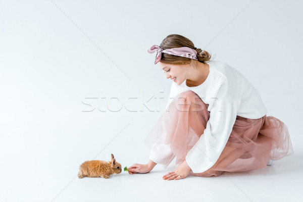 side view of beautiful smiling girl feeding furry rabbit isolated on white Stock photo © LightFieldStudios