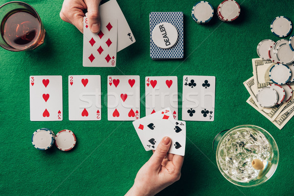 Men and woman playing poker by casino table with cards and chips Stock photo © LightFieldStudios