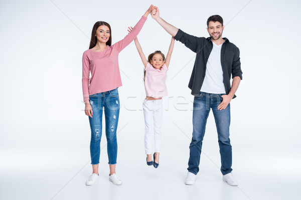 Happy little girl hanging on parents hands on white Stock photo © LightFieldStudios