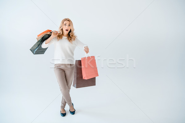 Shocked blonde woman holding shopping bags and looking at camera  Stock photo © LightFieldStudios