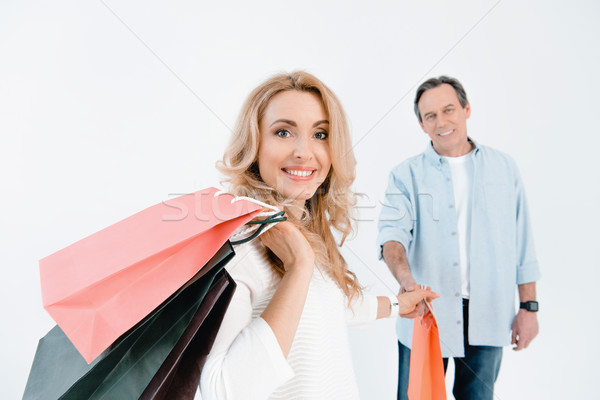 Mature man looking at happy blonde woman holding shopping bags  Stock photo © LightFieldStudios