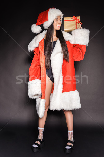 Woman in santa costume and swimsuit with present Stock photo © LightFieldStudios