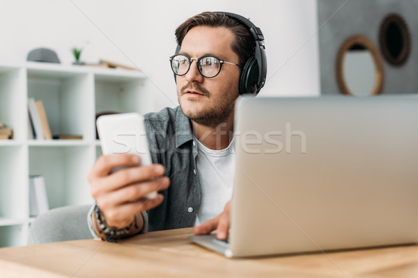 man in headphones using smartphone Stock photo © LightFieldStudios