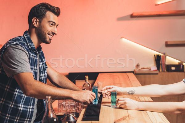 barman with alcohol shots on counter Stock photo © LightFieldStudios