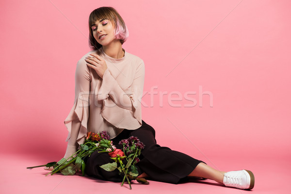 Young woman sitting on floor with bouquet Stock photo © LightFieldStudios