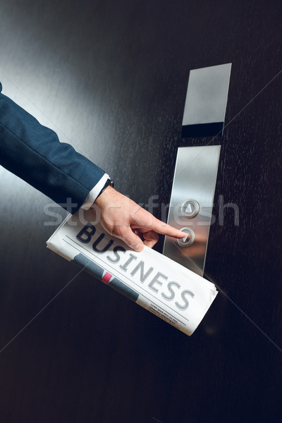 businessman with newspaper calling elevator Stock photo © LightFieldStudios