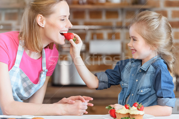 side view of daughter feeding mother with strawberry from cupcake Stock photo © LightFieldStudios
