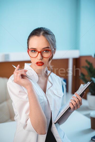 portrait of confident professional doctor in white coat and glasses holding notepad Stock photo © LightFieldStudios