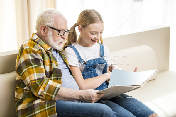 Happy grandfather and granddaughter reading book together at home Stock photo © LightFieldStudios