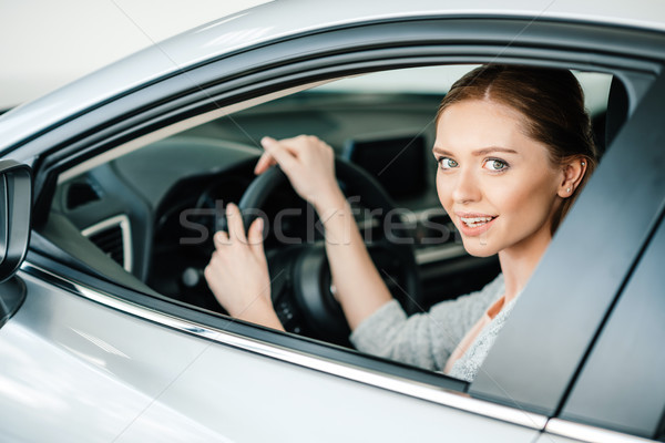 Attractive young woman sitting in new car and smiling at camera Stock photo © LightFieldStudios