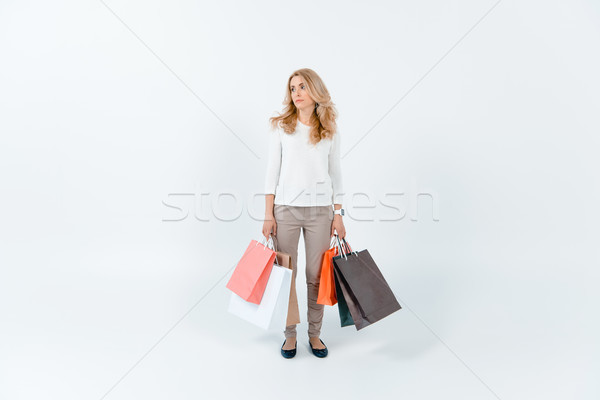 Tired blonde woman holding shopping bags and looking away on grey Stock photo © LightFieldStudios