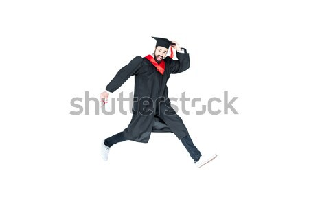 young student in graduation cap with diploma jumping isolated on white Stock photo © LightFieldStudios