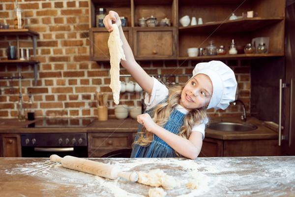 Megrémült kislány szakács sapka néz nyers lány Stock fotó © LightFieldStudios