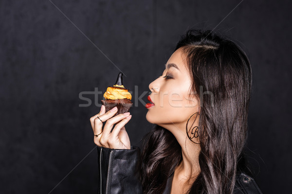 Stock photo: woman holding up halloween cupcake