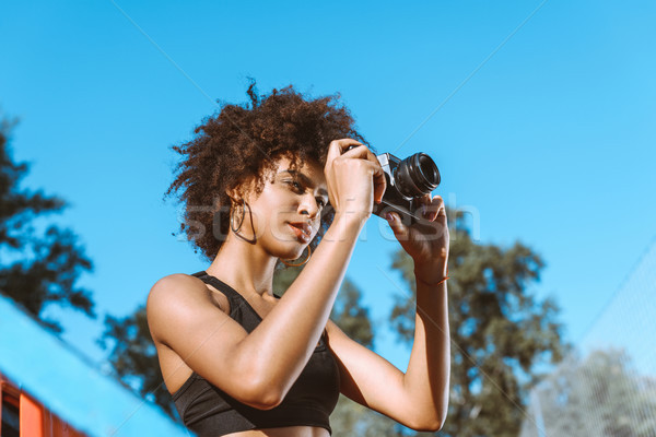 Athletic african-american woman with camera Stock photo © LightFieldStudios