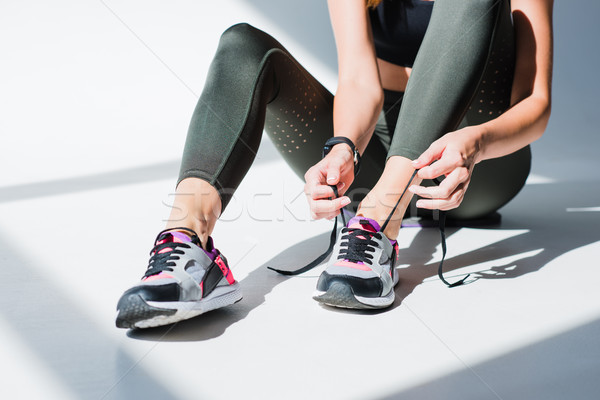 Stock photo: sportswoman tying shoelaces