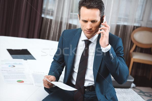 businessman holding paperwork and talking on phone Stock photo © LightFieldStudios