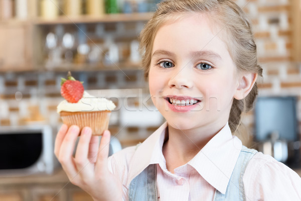 Happy little girl holding homemade cake and smiling at camera Stock photo © LightFieldStudios