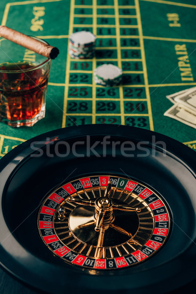 Casino table with roulette and glass with whiskey and cigar Stock photo © LightFieldStudios