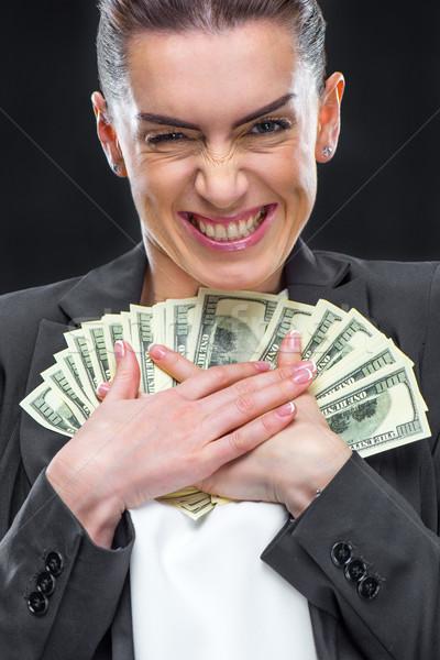 Businesswoman holding dollar banknotes Stock photo © LightFieldStudios