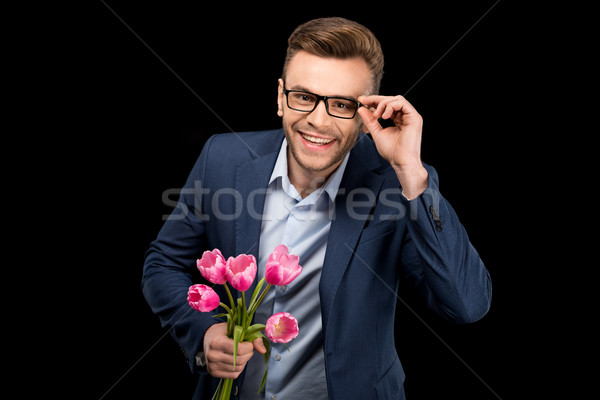 Smiling handsome man holding pink tulips and adjusting eyeglasses on black, international womens day Stock photo © LightFieldStudios