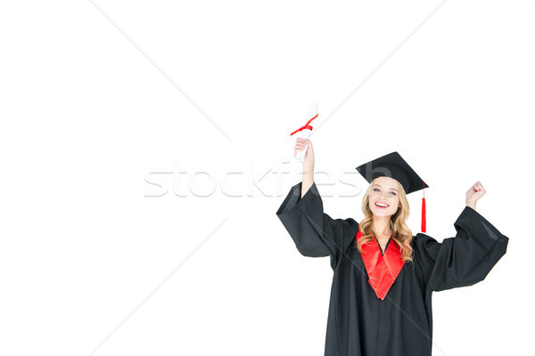 Young blonde woman in graduation gown holding diploma and triumphing on white  Stock photo © LightFieldStudios