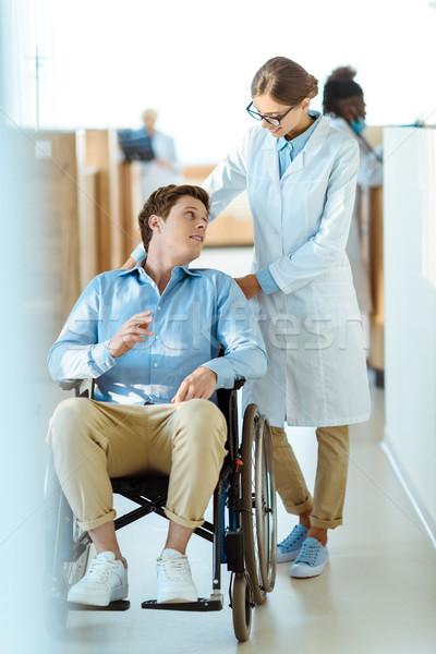 Doctor helping disabled man at hospital Stock photo © LightFieldStudios