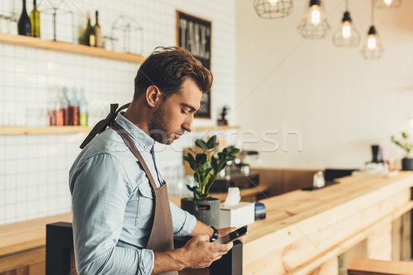 Barista okostelefon oldalnézet fókuszált fiatal áll Stock fotó © LightFieldStudios