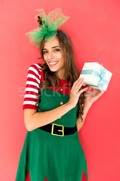 woman in elf costume with christmas gift Stock photo © LightFieldStudios