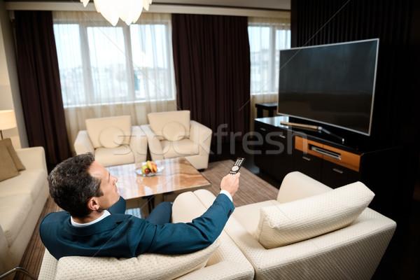 üzletember tv nézés hivatalos öltöny ül kanapé Stock fotó © LightFieldStudios