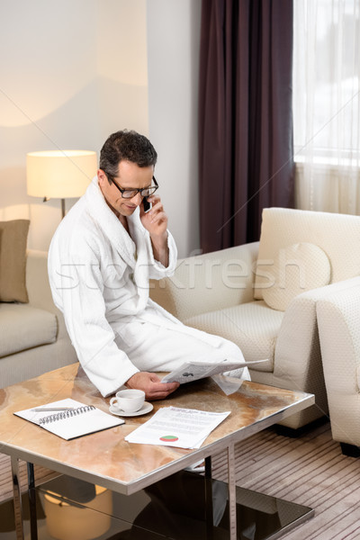 Businessman in bathrobe talking on phone Stock photo © LightFieldStudios