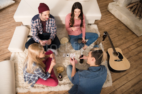 top view of men and women playing cards and eating popcorn at home Stock photo © LightFieldStudios