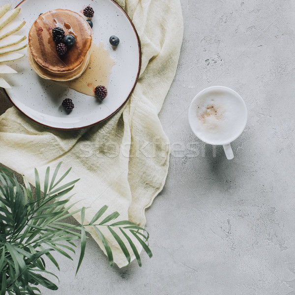 top view of tasty homemade pancakes with berries and cappuccino on grey  Stock photo © LightFieldStudios