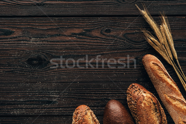 top view of arranged loafs of bread and wheat on wooden surface Stock photo © LightFieldStudios
