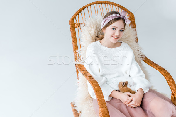 Stock photo: beautiful girl smiling at camera while holding rabbit and sitting in rocking chair isolated on white
