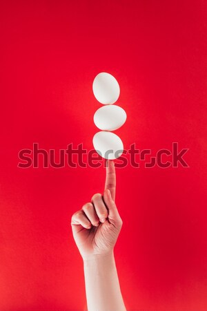 partial view of woman holding levitating raw chicken eggs on finger isolated on red Stock photo © LightFieldStudios