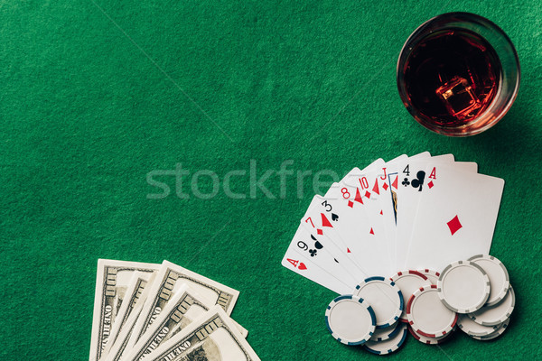 Money and cards with whiskey in glass on casino table Stock photo © LightFieldStudios
