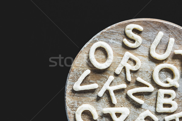 top view of letters made from cookie dough on wooden board with flour isolated on black Stock photo © LightFieldStudios