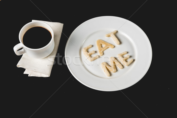 top view of eat me lettering made from cookie dough on plate with coffee cup isolated on black Stock photo © LightFieldStudios