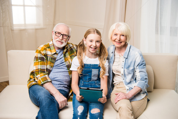Happy senior couple and cute smiling girl sitting together on sofa with digital tablet Stock photo © LightFieldStudios