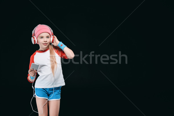 Cute sporty girl in headphones using smartphone isolated on black, activities for children concept   Stock photo © LightFieldStudios